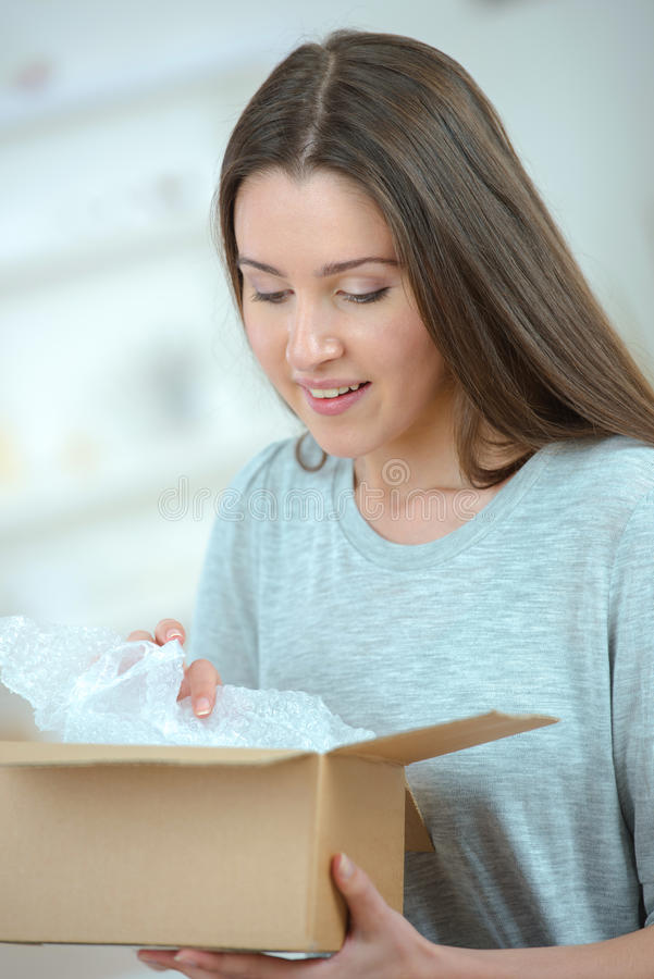 Pleasant woman opening box royalty free stock photography