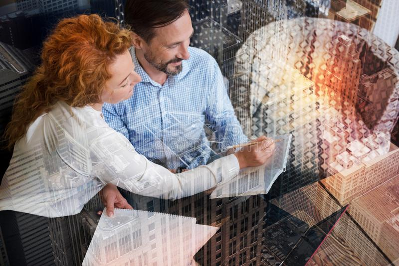 Pleasant woman suggesting corrections in her colleagues notes. Necessary corrections. The top view of a beautiful red-haired women sitting next to her colleague royalty free stock photo