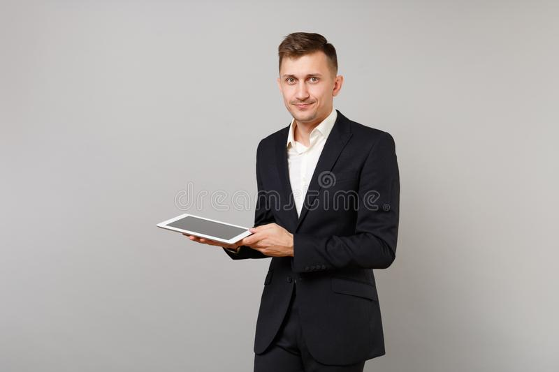 Pleasant young business man in classic black suit holding, using tablet pc computer with blank empty screen isolated on royalty free stock images