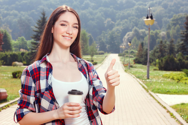 Pleasant young girl drinking coffee stock images