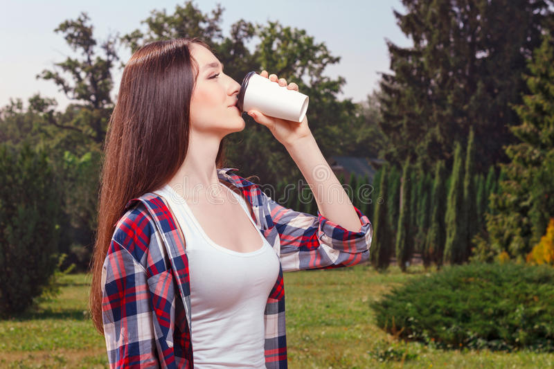 Pleasant young girl drinking coffee stock photography