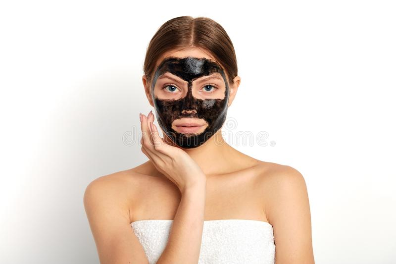 Pleasant young woman applying a mask on her face. Close up portrait, isolated white background, studio shot stock photography