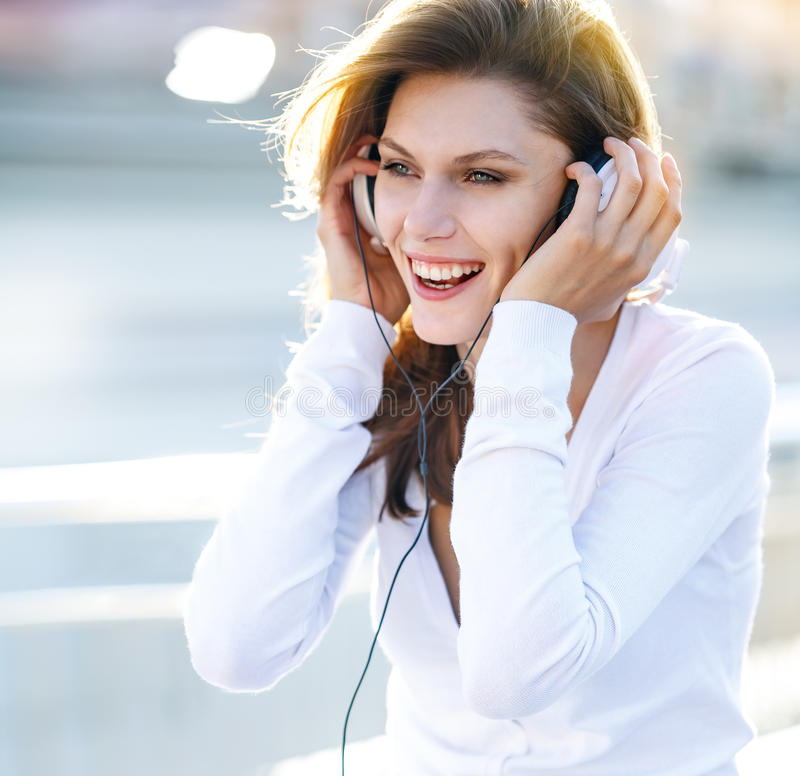 Pleasant young woman puts her headphones on. Smiling brunette girl in white clothes with white headphones looking at you stock photo