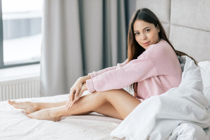 pleasant young woman in sweater posing to the camera stock photography