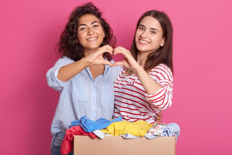 Pleasant young women wearing casual clothes posing isolated over pink background in studio. Females showing shape heart with hands stock photos