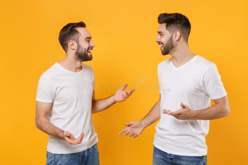 Pleasante jonge mannen vrienden in witte lege t-shirts die geïsoleerd zijn op gele oranje wand Mensen royalty-vrije stock afbeeldingen