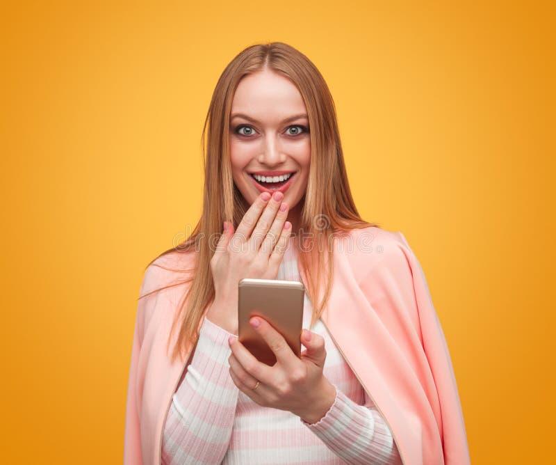 Pleasantly överraskningkvinna med smartphonen royaltyfri foto