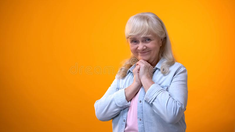 Pleasantly surprised senior woman flirting, receiving good news, sale discounts. Stock photo stock images