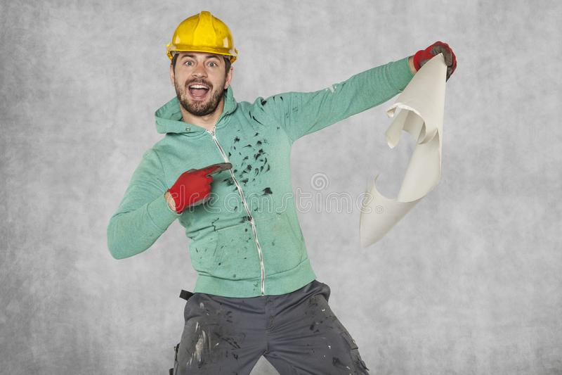 Pleasantly surprised worker indicates a construction plan royalty free stock image