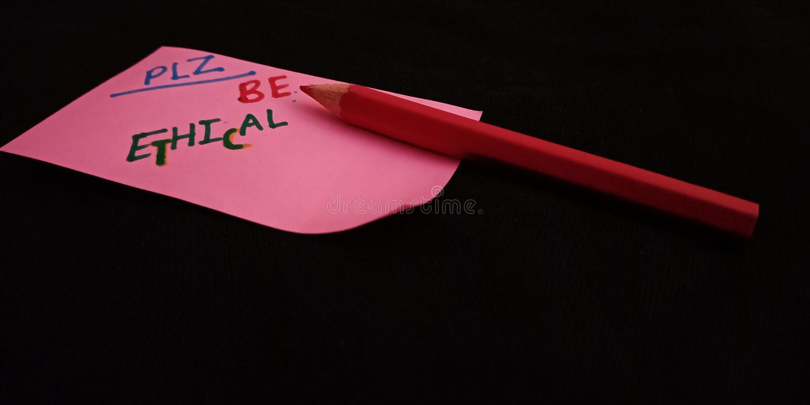 please be ethical concept displaying with red colour pencil on black background stock photo