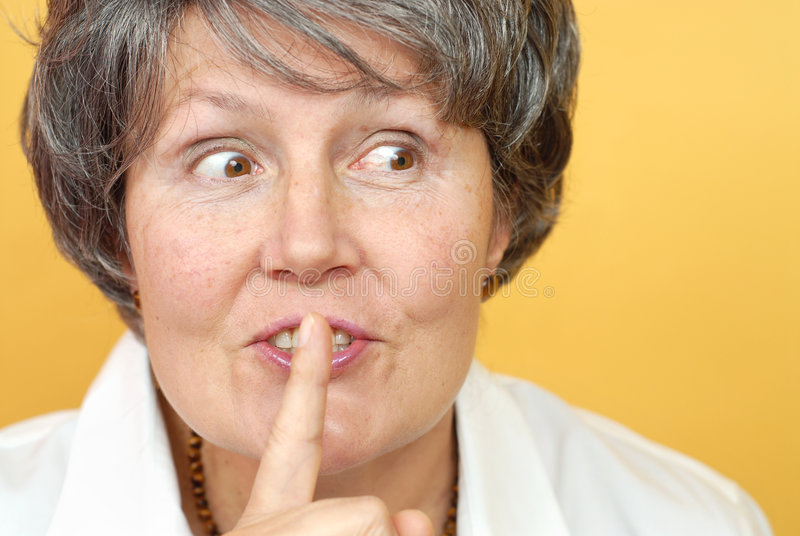 Please be quiet. Kind, attractive older librarian asking to please be quiet royalty free stock photo