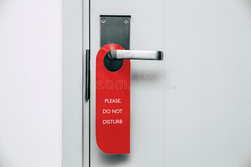 Do not disturb red hanging label at hotel room door knob. Please do not disturb red hanging label at hotel room door knob stock photos