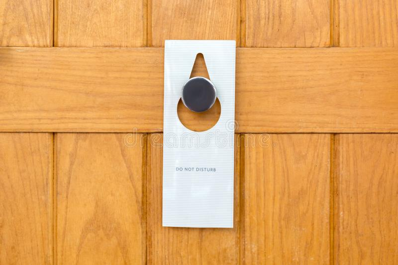 Please do not disturb sign on Closed wooden door of hotel room stock photo
