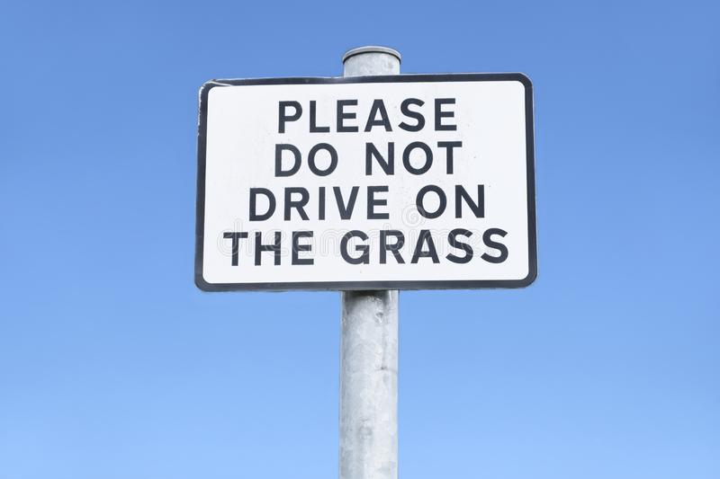 Please do not park on grass verge sign against empty blue sky. Uk royalty free stock image