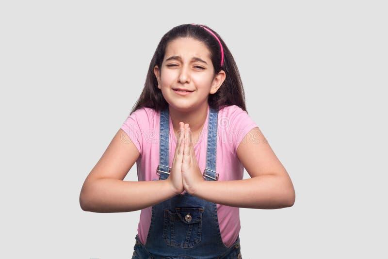 Please förlåter eller hjälper mig Stående av den ledsna bekymmerbrunettunga flickan i rosa t-skjorta och blått grov bomullstvillo royaltyfri bild