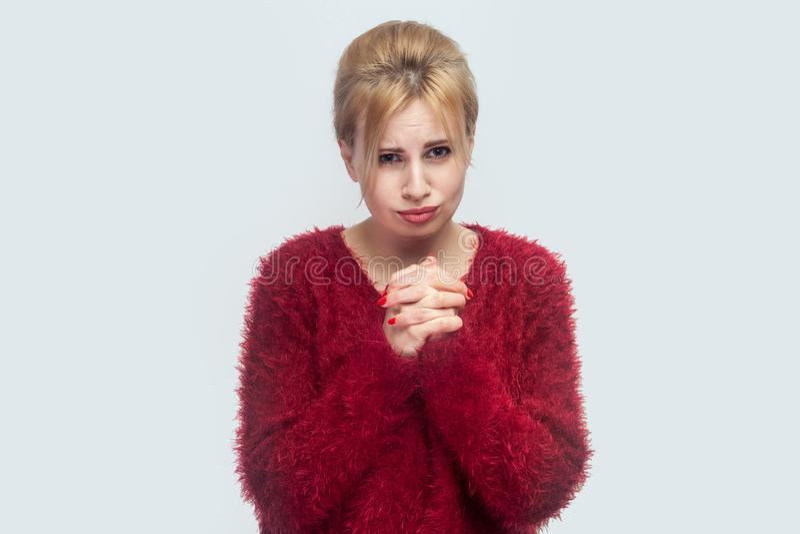 Please förlåter mig eller hjälp Stående av den ledsna hoppfulla härliga unga blonda kvinnan i den röda blusen som står och tigger fotografering för bildbyråer