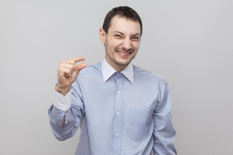 Please give me a few more. Portrait of handsome bristle businessman in classic light blue shirt standing and pleading for little stock photography