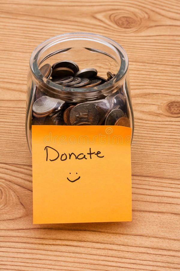 Please help by donating money. A jar full of change sitting on a wooden background, Please help by donating money stock photos