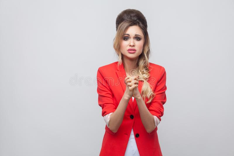 Please help me. Worried beautiful business lady with hairstyle and makeup in red fancy blazer, standing with palm hands and asking. To forgive or help. indoor stock image