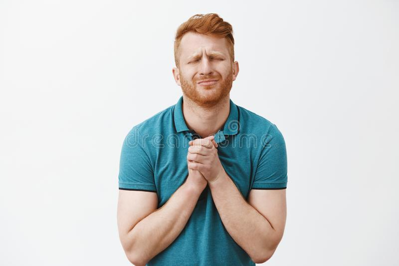 Please honey let me go with guys in pub. Redhead caucasian boyfriend with bristle in green t-shirt, closing eyes stock image