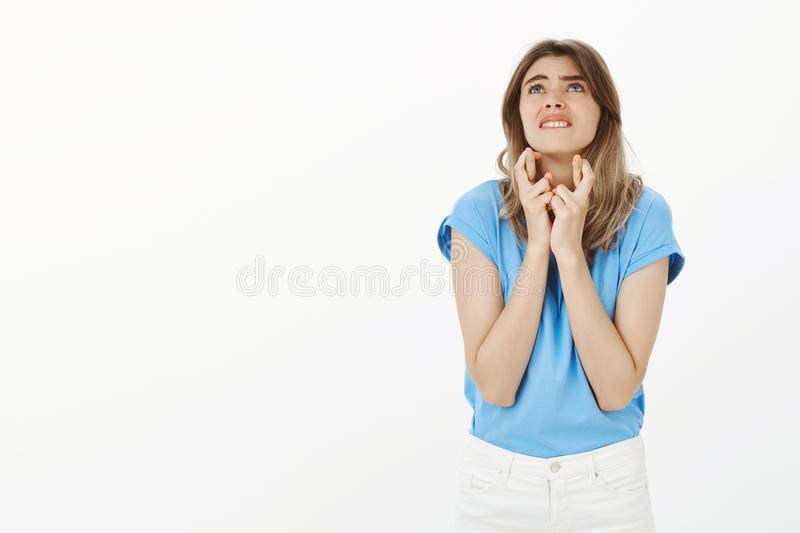 Please hope I will win. Intense hopeful young woman in trendy t-shirt, biting lip and looking up while crossing fingers stock photography