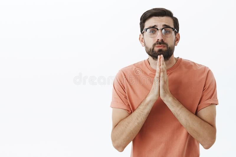 Please I need you help. Silly begging insecure nerdy guy in glasses stooping holding hands in pray gazing with cute sad stock image