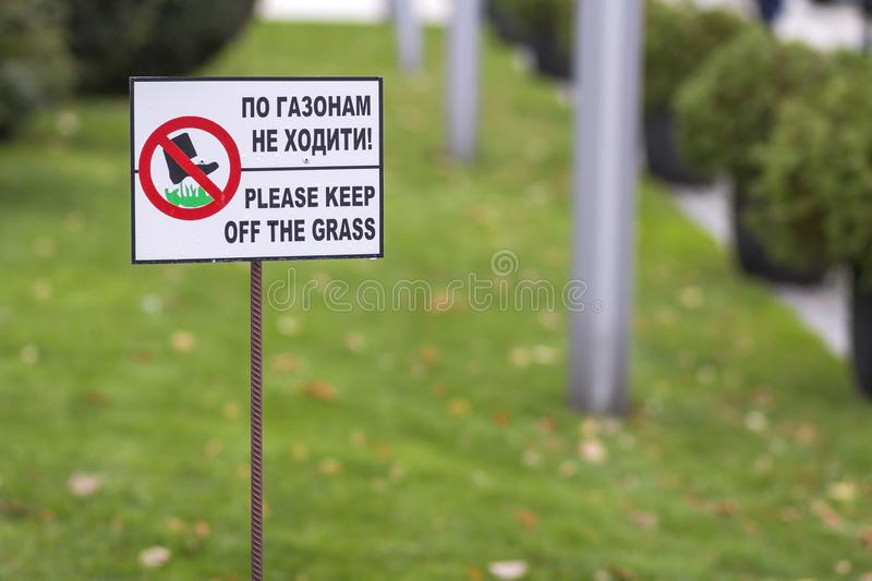 Please keep off the grass sign on green lawn grass blurred bokeh background on sunny summer day. City lifestyle and nature. Protection concept royalty free stock photography