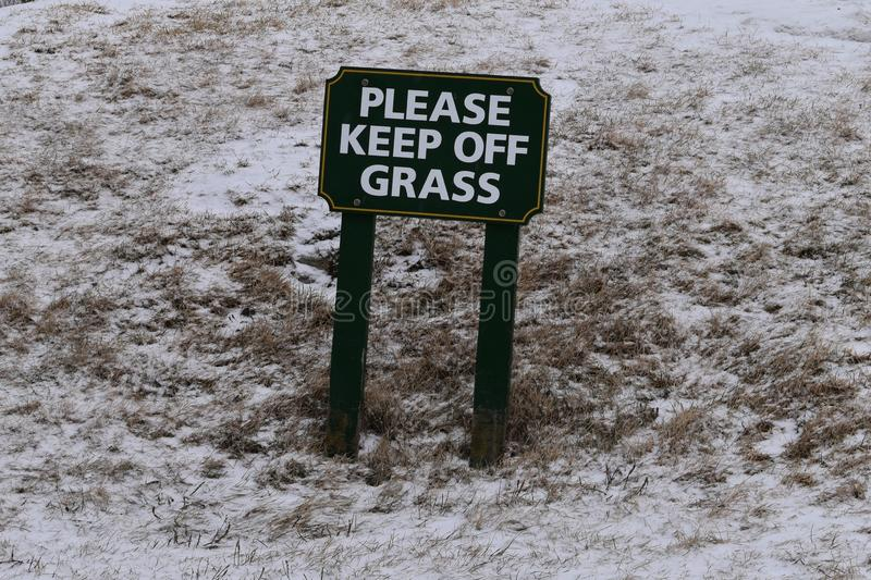 Please Keep Off Grass sign on snowy day, Cape Elizabth, Cumberland County, Maine, United States, New England US royalty free stock image
