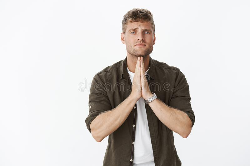 Please really need it. Portrait of handsome blond man begging holding hands in pray frowning in sorrow, looking hopeful royalty free stock image