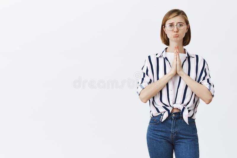 Please pay for me I have no money. Cute upset blond female in trendy glasses, holding hands in pray, pursing lips and stock image