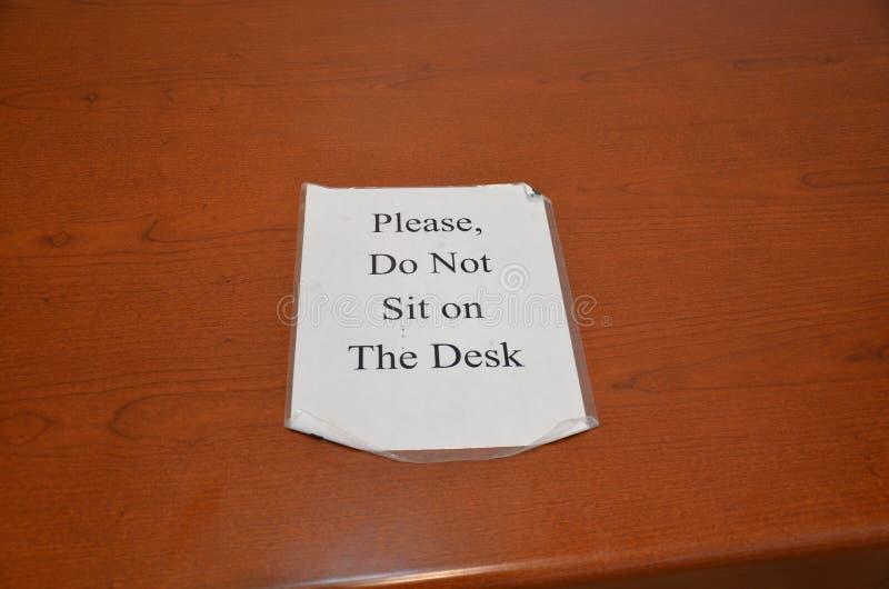 Please sitter inte på skrivbordtecknet på träskrivbordet royaltyfria bilder