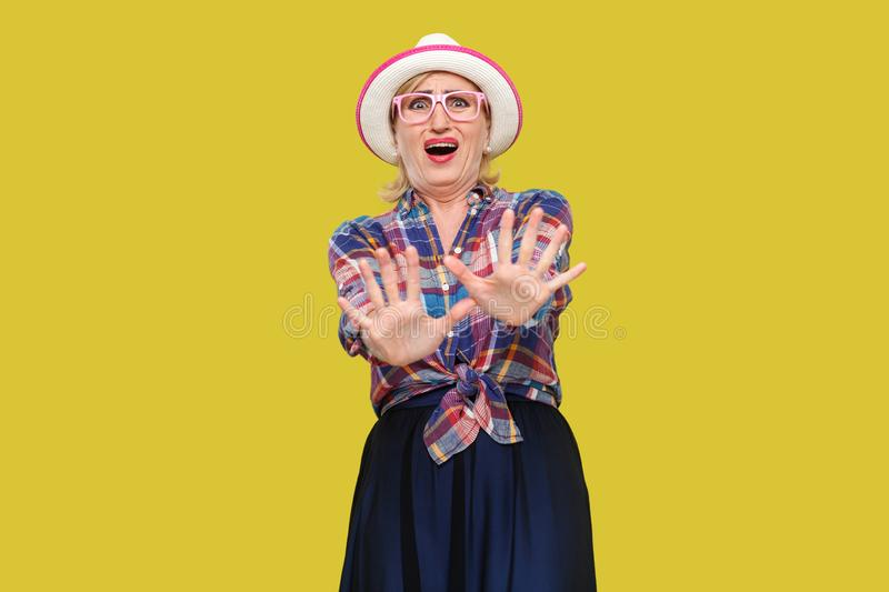 Please stop, i don`t need this. Portrait of scared modern stylish mature woman in casual style with hat and eyeglasses standing. With blocking hands and panic royalty free stock image