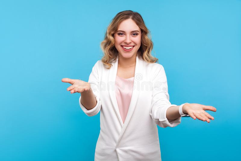 Please take! Portrait of kind cheerful woman raised hands as if sharing, giving for free. studio shot, blue background royalty free stock photography