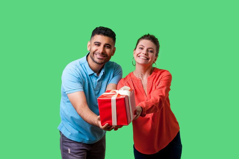Please take your present! Young generous couple giving gift box to camera. isolated on green background, indoor studio shot stock photography