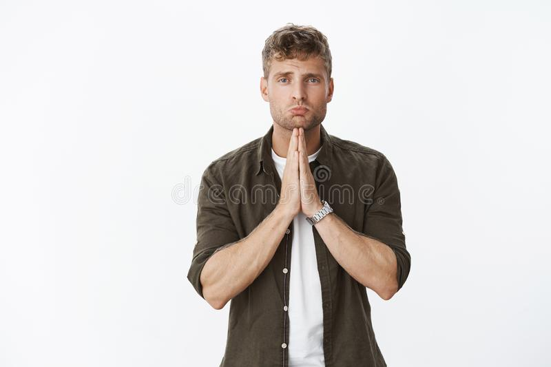 Please would you. Cute and sorrow blond guy pouting as asking forgiveness begging for favour or apology, standing in. Supplicating pose gazing with hopeful eyes stock photo