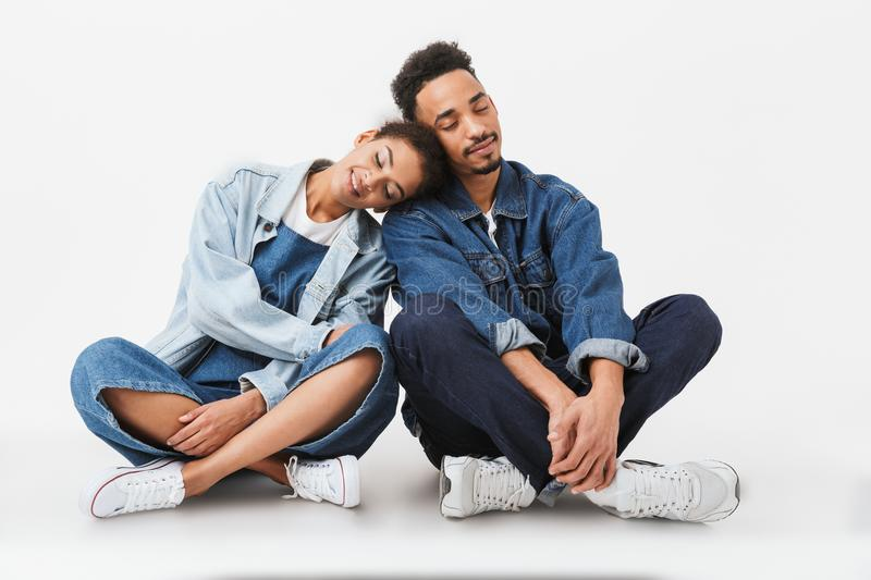 Pleased african couple in denim shirts sitting together on floor royalty free stock image