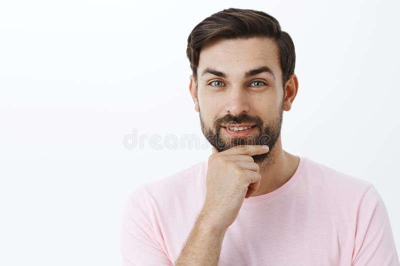 Pleased ambitious and charismatic handsome man rubbing beard smiling with delight at camera having interesting idea stock photos