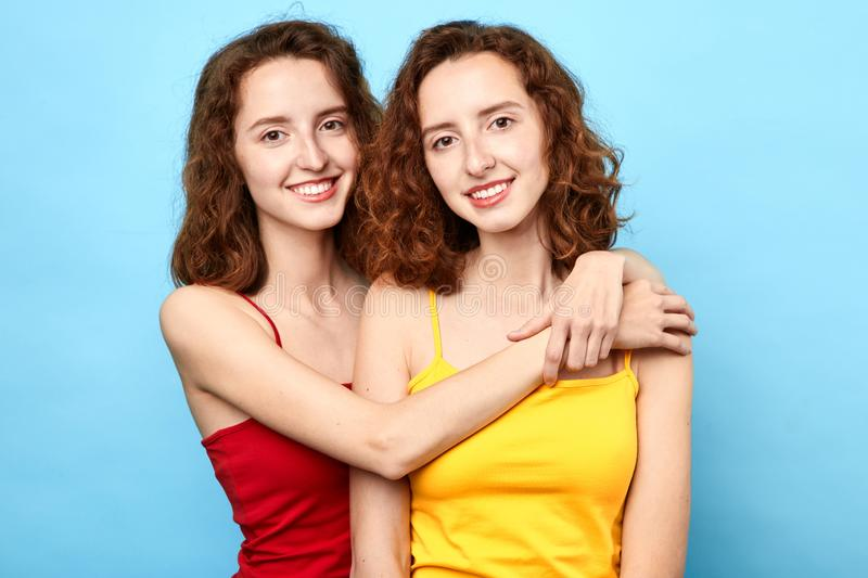 Pleased awesome twins wearing t-shirts hugging each other and looking at the camera over blue background stock photos