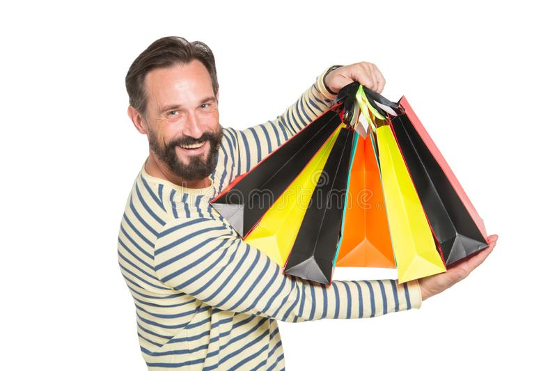 Pleased bearded man being satisfied with purchases. Positive bearded man being satisfied while holding carton bags with latest purchases and smiling broadly stock photo