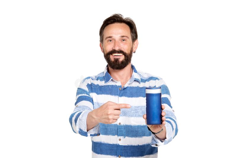 Pleased bearded man pointing at thermos cup in his hand. My recommendation. Mature bearded handsome man having cheerful mood while pointing at high quality stock photos