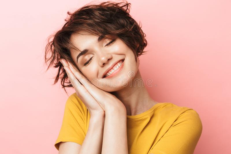 Pleased beautiful woman posing isolated over pink wall background ready to sleep stock photography
