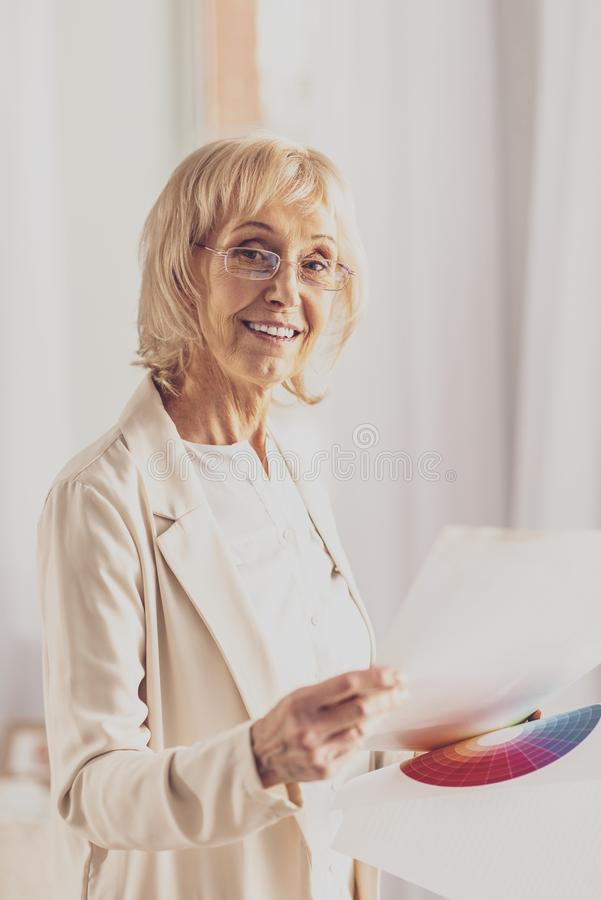 Pleased blonde preparing for presentation. Ready to work. Cheerful mature woman expressing positivity, posing on camera and holding papers royalty free stock photography