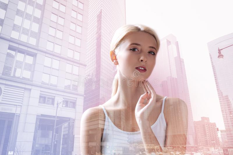 Pleased blonde standing against city background stock image