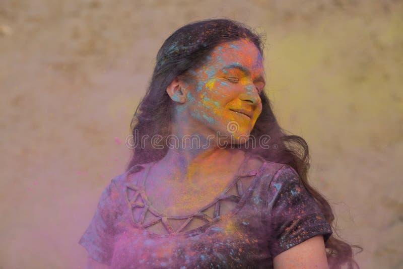 Pleased brunette model enjoying Holi festival at the desert. Woman posing with exploding dry paint stock photo