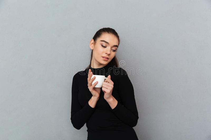 Pleased brunette woman in black clothes holding cup of coffee royalty free stock images