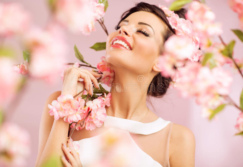 Pleased brunette woman among the flowers. Pleased brunette woman among the pink flowers stock image