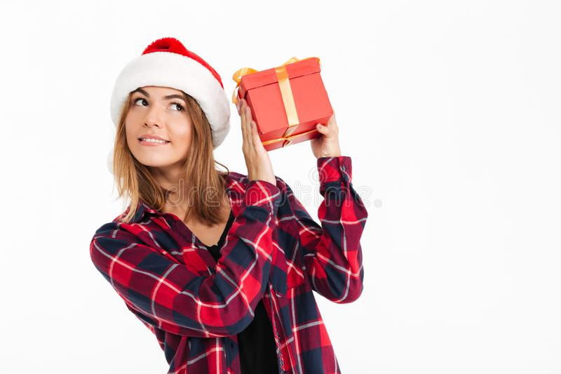 Pleased brunette woman in shirt and christmas hat holding gift royalty free stock image