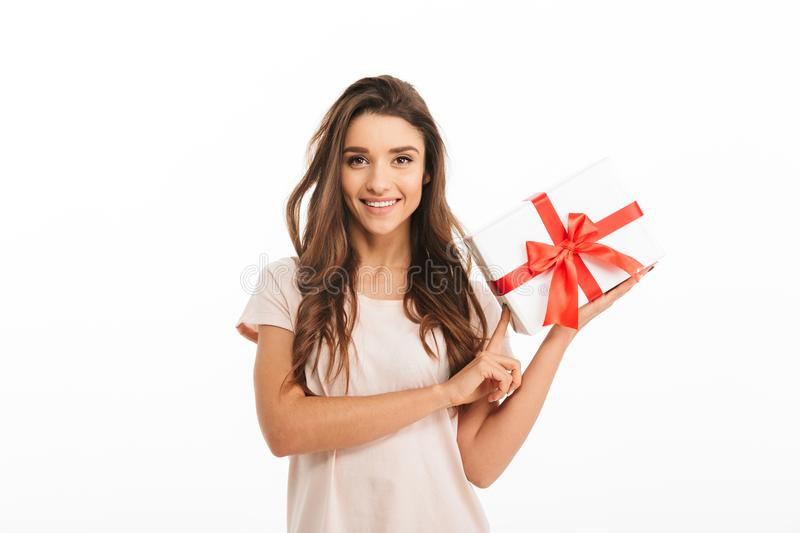 Pleased brunette woman in t-shirt holding gift box royalty free stock image