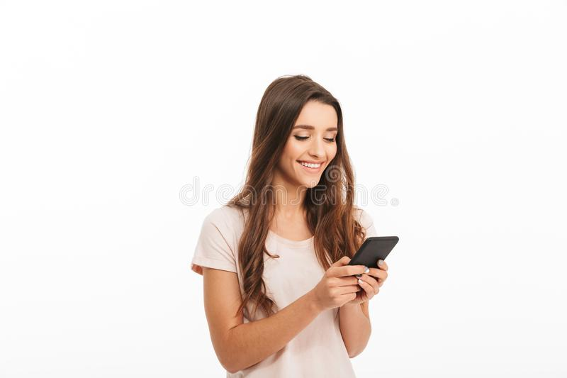 Pleased brunette woman in t-shirt writing message on smartphone royalty free stock images