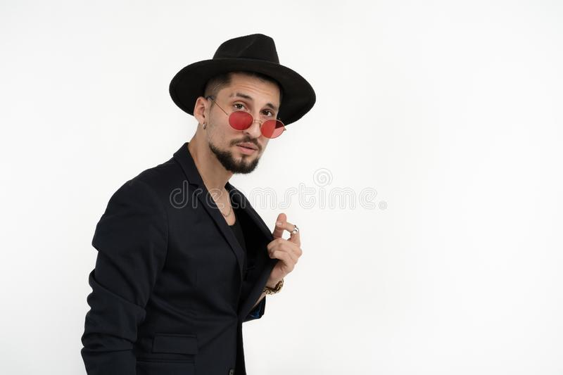 Pleased business man with beard in black suit and hat, in red sunglasses, holding jacket and looking at the camera royalty free stock photos